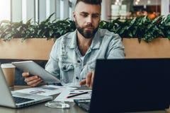 Hombre barbudo serio del inconformista que se sienta en oficina en el escritorio, trabajando en el ordenador portátil, sosteniend foto de archivo libre de regalías