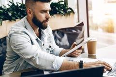 Hombre barbudo serio del inconformista que se sienta en oficina en el escritorio, trabajando en el ordenador portátil, sosteniend imagen de archivo