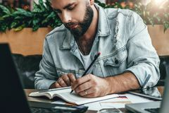 Hombre barbudo serio del inconformista que se sienta en oficina, haciendo notas en el cuaderno, trabajando El empresario analiza  fotografía de archivo libre de regalías