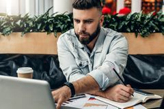 Hombre barbudo serio del inconformista que se sienta en oficina, haciendo notas en el cuaderno, trabajando El empresario analiza  imagenes de archivo
