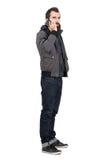 Hombre barbudo serio en chaqueta y sudadera con capucha que habla en el teléfono móvil que mira la cámara Foto de archivo