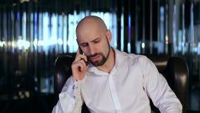 Hombre barbudo serio que habla en el primer del teléfono metrajes