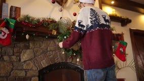 Hombre barbudo sonriente en guirnalda colgante kniited de la Navidad del suéter sobre la chimenea adornada con la guirnalda que d metrajes