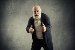Hombre barbudo sonriente que muestra los pulgares para arriba Foto de archivo libre de regalías
