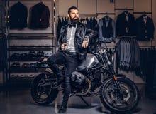 Hombre barbudo tatuado elegante con vestido en chaqueta de cuero negra y la corbata de lazo que presentan cerca de la moto retra  imagenes de archivo