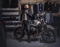 Hombre barbudo tatuado elegante con vestido en chaqueta de cuero negra y la corbata de lazo que presentan cerca de la moto retra  imagen de archivo libre de regalías