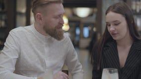 Hombre barbudo y mujer morena bonita que se sientan en el restaurante en la tabla El hombre muestra su información de la novia almacen de video