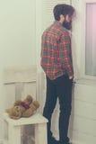 Hombre barbudo y oso de peluche marrón lindo con el corazón rojo Foto de archivo