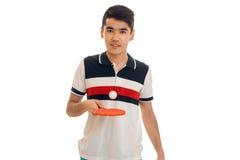 Hombre bastante joven del brunett que juega a ping-pong y que mira la cámara aislada en el fondo blanco Imagen de archivo