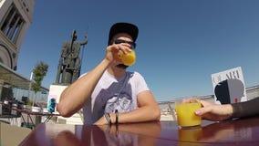 Hombre beardy hermoso del inconformista que bebe el zumo de naranja en la barra Madrid del tejado almacen de metraje de vídeo