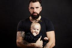 Hombre beared tatuado hermoso que detiene al pequeño bebé lindo en fondo negro Fotos de archivo