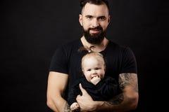 Hombre beared tatuado hermoso que detiene al pequeño bebé lindo en fondo negro Foto de archivo libre de regalías