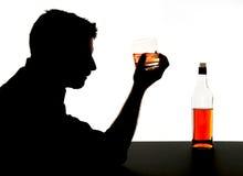 hombre bebido alcohólico con el vidrio del whisky en silueta de la adicción al alcohol Foto de archivo
