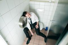 Hombre bebido durmiente de los jóvenes en el toilette imagen de archivo libre de regalías