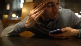 Hombre bebido que despierta en la tabla en restaurante después del partido, llamando el taxi, resaca metrajes