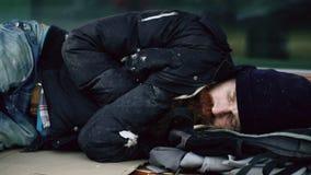 Hombre bebido sin hogar joven que intenta dormir en la cartulina en banco en la acera imagenes de archivo