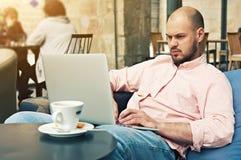 Hombre bien vestido joven que hace las compras en línea, sentada en la mesa de desayuno en un café imagenes de archivo