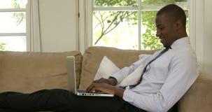 Hombre bien vestido que sonríe mientras que usa el ordenador portátil