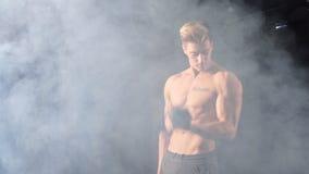 Hombre blanco descamisado que comienza ejercicio con el peso de la pesa de gimnasia en gimnasio oscuro almacen de video