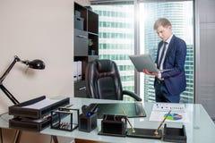 Hombre blanco en oficina con el ordenador portátil en fondo de la ciudad Concepto de las finanzas de la tecnología del negocio fotografía de archivo libre de regalías