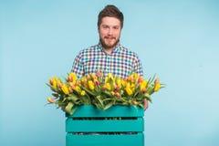Hombre blanco hermoso que sostiene una caja con los tulipanes amarillos en fondo azul imágenes de archivo libres de regalías