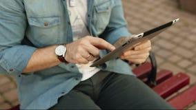 Hombre bonito del inconformista que se sienta en banco usando la tableta al aire libre almacen de video
