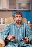 Hombre borracho con el vidrio y el telecontrol imágenes de archivo libres de regalías