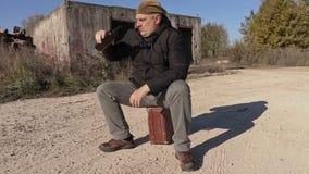 Hombre borracho con la botella de vino vacía que se sienta en la maleta almacen de video