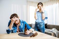 Hombre borracho con la mujer en casa foto de archivo