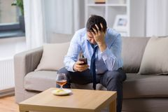 Hombre borracho con smartphone y alcohol en casa fotografía de archivo
