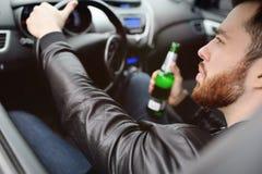 Hombre borracho con una botella de cerveza que conduce un coche fotografía de archivo