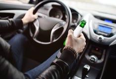 Hombre borracho con una botella de cerveza que conduce un coche imagen de archivo