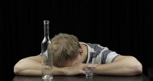 Hombre borracho deprimido que duerme solamente en un cuarto oscuro Concepto de alcoholismo imagen de archivo