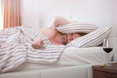 Hombre borracho en cama Fotografía de archivo