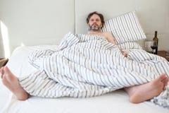 Hombre borracho en cama fotografía de archivo libre de regalías
