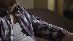 Hombre borracho en su 40s que se sienta en el sofá con la botella de cerveza y que duerme, alcoholismo metrajes