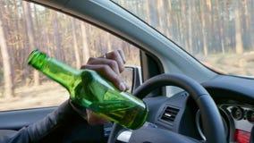Hombre borracho que conduce el coche con una botella de cerveza en su mano en cierre para arriba metrajes