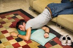 Hombre borracho que descansa sobre el sofá con la cabeza en el piso Foto de archivo