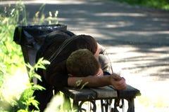 Hombre borracho que duerme en parque en banco de madera imagen de archivo