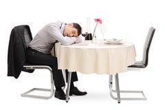 Hombre borracho que duerme en una tabla del restaurante foto de archivo