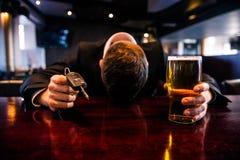 Hombre borracho que lleva a cabo llaves de una cerveza y del coche imagen de archivo