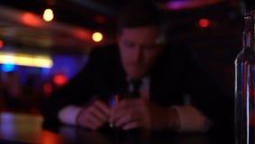 Hombre borracho que miente en el contador solo, forma de vida frívola, concepto de la barra del alcoholismo almacen de metraje de vídeo