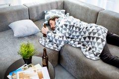 Hombre borracho que miente en el sofá un hogar imagen de archivo