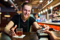 Hombre borracho que paga vía NFC en Pub fotografía de archivo