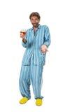 Hombre borracho que se coloca en pijamas con el vidrio Fotos de archivo