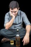 Hombre borracho que se sienta en el piso con un vidrio y una botella de liquo Foto de archivo libre de regalías