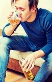 Hombre borracho que se sienta en el sofá y el whisky de consumición foto de archivo