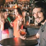 Hombre borracho que se sienta en la barra, cóctel de consumición, mirando a muchachas Foto de archivo