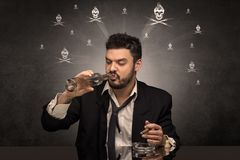 Hombre borracho que se sienta en la tabla con concepto de los cr?neos fotos de archivo libres de regalías