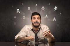 Hombre borracho que se sienta en la tabla con concepto de los cr?neos imágenes de archivo libres de regalías